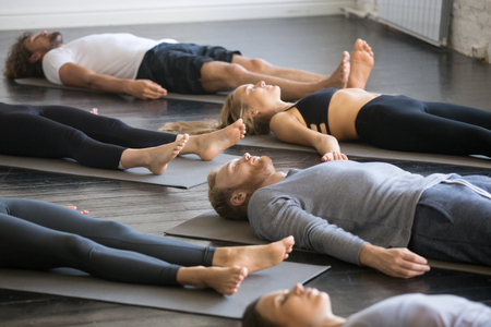 Group of young sporty people practicing yoga lesson with instructor in gym, lying in Dead Body exercise, doing Savasana, Corpse pose, friends relaxing after working out in sport club, indoor image Stockfoto
