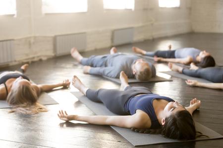 시체 운동 Savasana 포즈를 하 고, 체육관에서 요가 수업을 연습하는 젊은 스포티 한 사람들의 그룹, 스포츠 클럽, 실내 이미지에서 밖으로 작동 후 편안