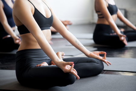 Group of young sporty people, students practicing yoga lesson with instructor, sitting meditating in Lotus pose, friends working out in club, indoor close up image. Wellbeing and wellness concept