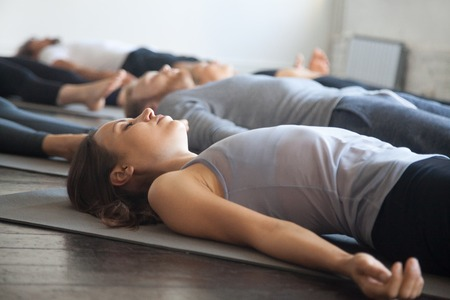 Group of young sporty people practicing yoga lesson with instructor in gym, lying in Dead Body exercise, doing Savasana, Corpse pose, friends relaxing after working out in sport club, studio image Banque d'images