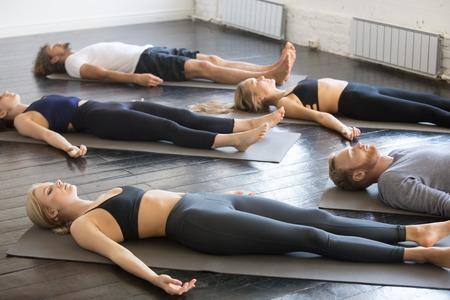 체육관에서 강사와 요가 수업을 연습하는 젊은 스포티 한 사람들의 그룹, 죽은 시체 운동, 거짓말 Savasana, 시체 포즈, 스포츠 클럽, 스튜디오 이미지에