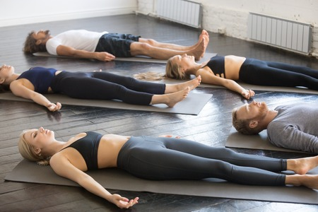 Group of young sporty people practicing yoga lesson with instructor in gym, lying in Dead Body exercise, doing Savasana, Corpse pose, friends relaxing after working out in sport club, studio image Archivio Fotografico