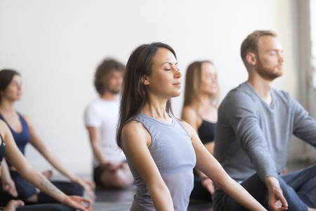 Group of young people, sporty students practicing yoga lesson with instructor, sitting and meditating with closed eyes in Padmasana exercise, Lotus pose, friends working out in club, studio background Stockfoto