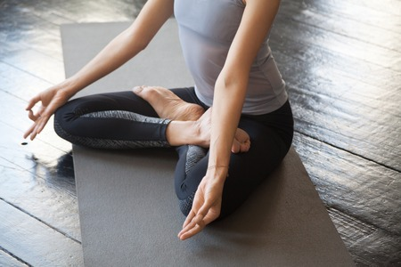 Close up of sporty young woman practicing yoga, sitting in Lotus exercise, Padmasana pose with mudra, working out wearing sportswear, studio floor background. Wellbeing and wellness concept Stock Photo