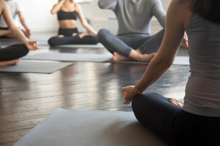 Young sporty people practicing yoga lesson with instructor, sitting, making Alternate Nostril Breathing, nadi shodhana pranayama exercise, working out, close up image. Wellbeing and wellness concept Stockfoto