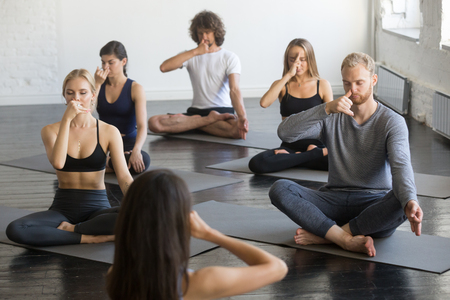 Group of young sporty people practicing yoga lesson with instructor, making nadi shodhana pranayama exercise sitting in Sukhasana pose, friends working out in gym, studio. Wellbeing, wellness concept Stock Photo