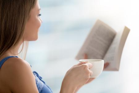 Mujer joven que lee el libro de papel interesante en casa mientras que sostiene la taza de café por la mañana, muchacha feliz que disfruta del último bestseller más nuevo que pasa tiempo con la literatura, amante novela romántica, cierre para arriba Foto de archivo - 87571921