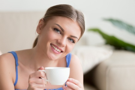 Young smiling attractive woman enjoying instant brewed coffee in the morning, happy lady holding cup of tea and looking at camera, pleasant day at home with hot drink in mug, head shot portrait Stock Photo