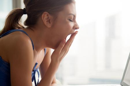Jonge verveelde vrouw die dichtbij laptop thuis huisvest die mond behandelt met hand, slaperige student die van het besteden van teveel tijd met computer wordt vermoeid, die slaperig lijden aan gebrek aan slaap, zijaanzicht hoofdschot voelt