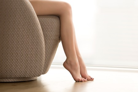 Close up view of beautiful bare female legs, young woman sitting barefoot on cozy chair relaxing at home, enjoying soft waxed skin, foot rest, no shoes, epilation and depilation, copy space Banco de Imagens