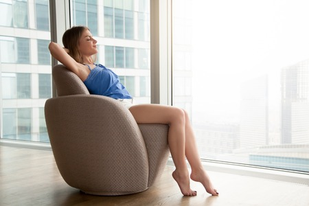designer: Relaxed young woman resting on comfortable armchair with eyes closed hands behind head at home, happy lady relaxing in cozy designer chair near full-length window with city view, time for yourself