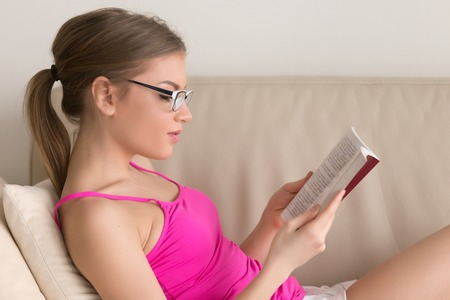 Young woman enjoying fiction book on sofa at living room, attractive hipster girl in glasses for reading immersed in new bestseller or classic novel, student studying course literature before exam