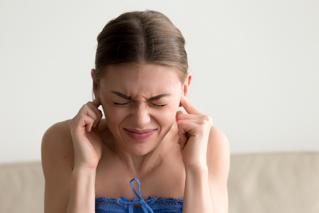 Young annoyed woman sticking fingers in ears with eyes closed, not listening to loud noise, ignoring stressful environment, stubborn teen refuses hearing, feels ear ache, tinnitus, head shot portrait