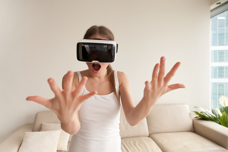 Surprised amazed young woman wearing VR glasses looking at her own hands seem so real through goggles, exciting first virtual reality experience, teen girl shocked by futuristic augmented world Imagens