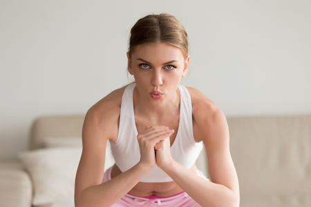 Young sporty slim woman doing squat morning exercise, practicing breathing correctly during working out home routine, looking at camera, holding hands together exhaling on muscular exertion, portrait
