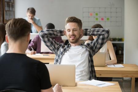 笑顔若い男性起業家共有オフィスで職場に戻ってストレッチをリラックスします。仕事の概念は、プロジェクトを終えた重いワークフロー、肯定的
