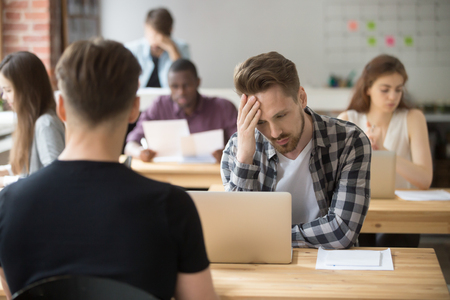 tired: Perplexed, puzzled casual entrepreneur looks at laptop screen at workplace in shared office. Young project manager made serious mistake, lost documents due to computer crash, difficult business task.