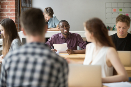 african business: Young smiling african american entrepreneur talking to female coworker. Multiethnic team of colleagues communicate during workflow, employee inquiring about work strategy, specifics in business plan.