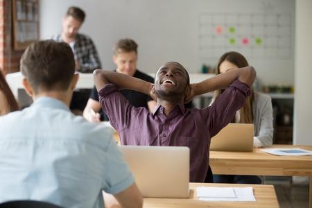 편안한 아프리카 계 미국인 기업가 행복하게 완료 작업 후 쉬고 머리 뒤 손으로 휴식. 그의 동료 앞에 작업을 수행하는 회사원, 동료 공유 사무실에서