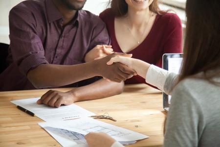 Afroamerikanermann, der Hände mit Immobilienagentur, Vertrag und Schlüsseln auf Tabelle rüttelt. Ehemann und Frau unterschrieben Mietvertrag. Junge multiethnische Paare kauften neues Hauptkonzept. Nahaufnahme