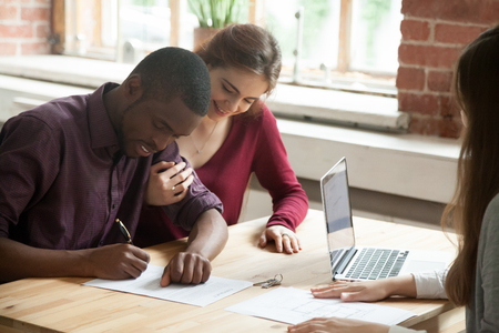 African american man signing home purchase agreement in front of realtor, his smiling wife watching contract being signed. Young multiethnic family leasing new apartment. First time buyers concept. Stock Photo