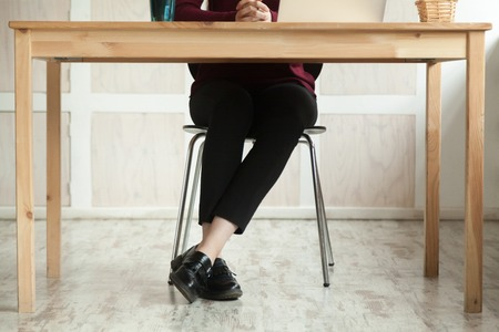Close up legs of business lady at work desk anticipating meeting. Businesswoman preparing for briefing, having audition. Human resources specialist calmly sitting waiting for job candidate to arrive.