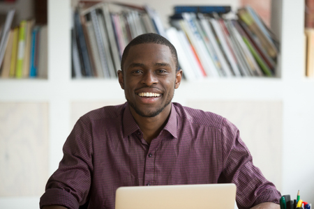 african business: Head shot portrait of smiling handsome african american businessman. Young casually dressed freelance business owner, office worker looks at camera, positive attitude during job interview or meeting.
