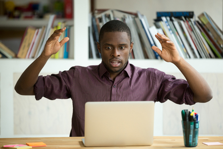 Shocked young african american office worker looking at laptop screen throwing arms in the air. Horrified small business owner sees app error, lost documents because of unexpected bad computer crash. Banco de Imagens