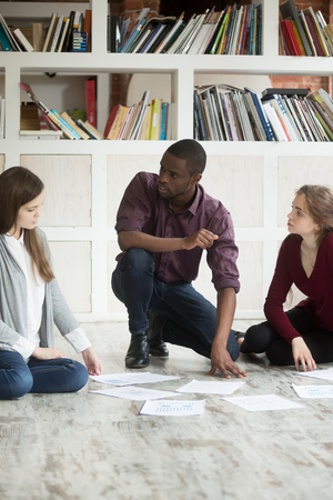 african business: Multiethnic business team collaborating on project together. African american man and two young women sitting on the floor with financial documents lying around. Project manager coaching coworkers.