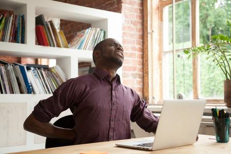 Junge erschöpften den männlichen Büroangestellten des Afroamerikaners, der Rückenbeschwerden am Arbeitsschreibtisch im Büro hat. Ermüdeter zufälliger Geschäftsmann, der Rückenschmerzen sich fühlt, nachdem er stundenlang auf unbequemem Stuhl sitzt. Standard-Bild