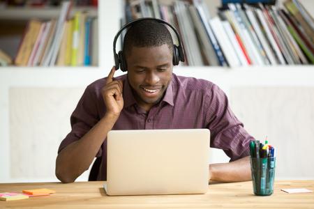 Glimlachende Afrikaanse Amerikaanse beambte in hoofdtelefoons die laptop het scherm bekijken. Jonge toevallige zakenman die vreemde taal bestudeert, die met cliënten door videoconferentietoepassing communiceert.