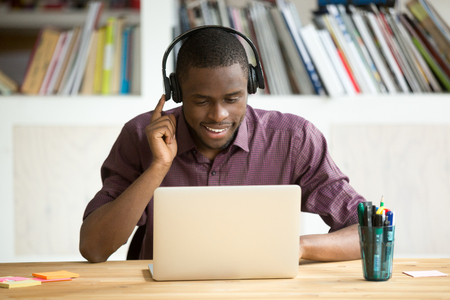 Smiling african american office worker in headphones looking at laptop screen. Young  casual businessman studying foreign language, communicating with clients through video conference application. Standard-Bild