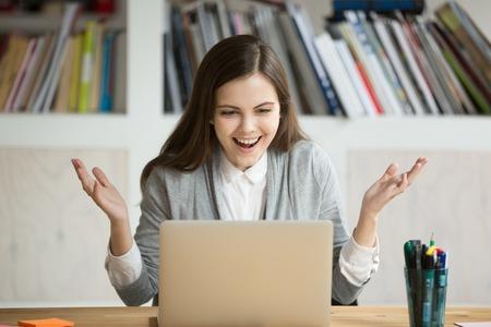 Jonge zakenvrouw kijkt laptop scherm met expressie van vreugde en opwinding. Verraste vrouwelijke beambte die op het werk computer met grote glimlach bekijkt. Zakenvrouw ontvangen promotie. Stockfoto