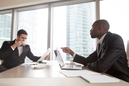African american businessman conducting negotiations, explaining terms of contract, discussing financial plans or results with caucasian partner. Financial consultant talking with investor in office