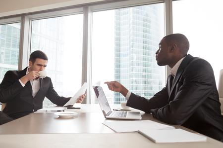 Afrikaanse Amerikaanse zakenman die onderhandelingen voert, die termijnen van contract verklaart, die financiële plannen of resultaten bespreken met Kaukasische partner. Financiële adviseur die met investeerder in bureau spreekt Stockfoto
