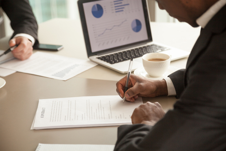 Close up photo of african american businessman sitting at office desk in front of laptop with financial infographics and singing contract document. Black entrepreneur concluding agreement, making deal
