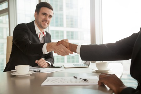african american handshake: Close up image of multinational business partners shaking their hands after singing contract at desk in office. Successful business negotiations, accepting good offer, full trust between businessmen