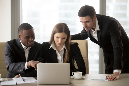 Group of millennial multinational business leaders discussing details of new project while working together on laptop in meeting room. Young businesswoman making presentation to multi-ethnic partners Фото со стока