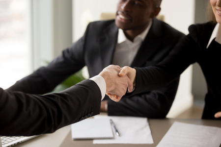 Close up image of business handshake between caucasian businesswoman and client or partner on multinational meeting in office. Job applicant introducing himself to company HR management on interview