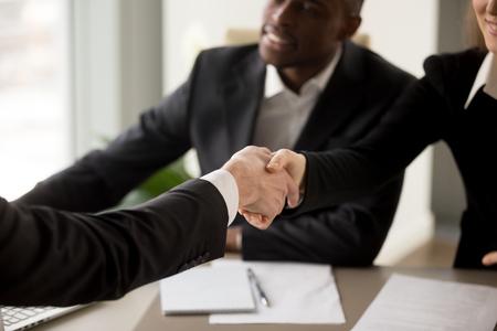 Sluit omhoog beeld van bedrijfshanddruk tussen Kaukasische onderneemster en cliënt of partner op multinationale vergadering in bureau. Sollicitant die zich bij het HR-management van de onderneming op interview introduceert