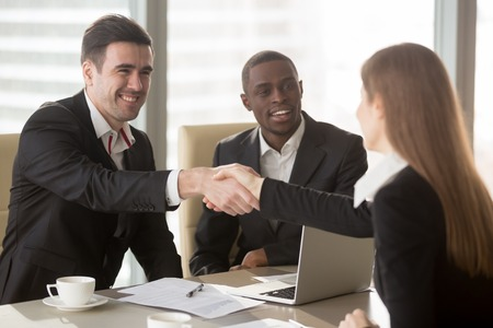 Happy smiling caucasian and afro american businessmen handshaking with female job applicant or businesswoman on meeting in office. Greetings on start or after conclusion of negotiations or interview