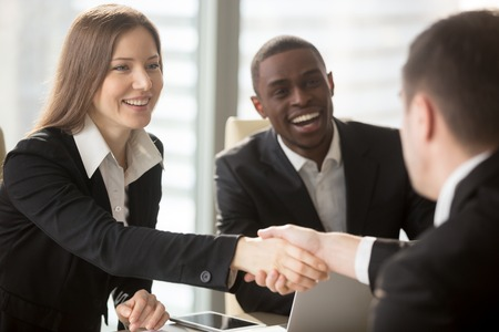 Mooie glimlachende onderneemster met Afrikaanse Amerikaanse partner het schudden hand en het welkom heten van nieuw teamlid, bedrijfsmetgezel of baankandidaat. Bedrijf recruiters blij om goede positie kandidaat te zien Stockfoto