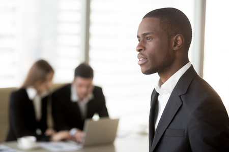 Side view portrait of handsome black businessman looking in distance, caucasian businesspersons working on laptop at office desk on background. Employment opportunities for african americans concept