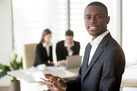 Portrait of smiling african american businessman using digital tablet and looking at camera, caucasian colleagues using laptop on background. IT startup multinational team, gadget for business concept
