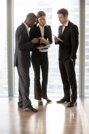 Group of multinational employee talking about business, preparing to meeting. Two political PR specialist giving instructions and helping politician with theses before his public speaking or interview Stock fotó