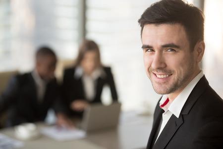 Headshotportret van succesvolle Kaukasische zakenman die camera, zwarte man en witte vrouw bekijken die laptop op achtergrond met behulp van. Glimlachende bedrijfsleider die bij het ontmoeten van multinationale partners stellen Stockfoto