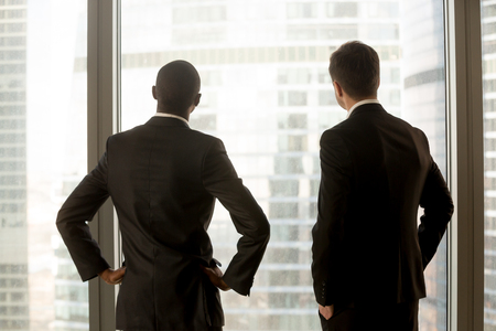 Two multinational businessmen standing together and looking in window at office. African american and caucasian business partners thinking about perspectives, dreaming of success, planning future deal