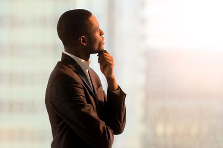 Portret van peinzende Afrikaanse Amerikaanse zakenman die zich dichtbij venster bevindt en over besluit denkt, dat van succes droomt, nadenkend nieuw opstarten. Knappe zwarte bedrijfsleider die bedrijfstoekomst veronderstelt