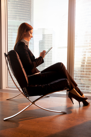 Female company leader using digital tablet while sitting in soft chair near window on sunset. Businesswoman working online with modern electronic gadget, resting with phablet in hotel room in evening Stock Photo