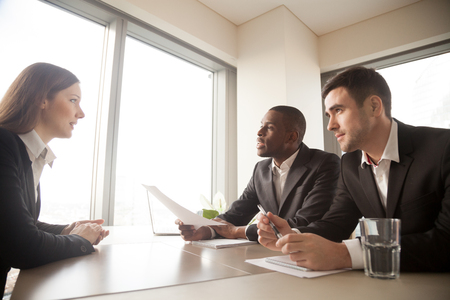 Multinational hiring managers conducting interview with caucasian young woman in formal wear. Millennial female candidate answering questions on meeting with employers, telling about work experience Stock Photo